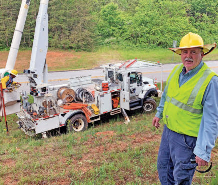 utility worker standing in front of bucket truck near a road