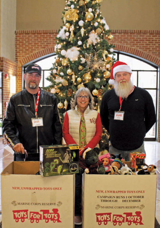 Toys for Tots coordinators Keith Hackett and Amos Smith pick up donations from HEMC's Susan Carney