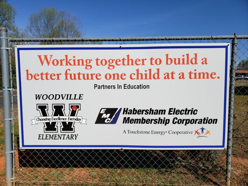 "Sign on a fence: ""Working together to build a better future one child at a time. Partners in Education. Woodville Elementary — Choosing Excellence Everyday. Habersham Electric Membership Corporation. (A Touchstone Energy Cooperative)."""